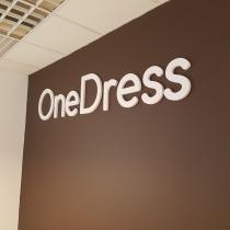 One Dress logotipas ant sienos pagamintas iš PVC plastiko.